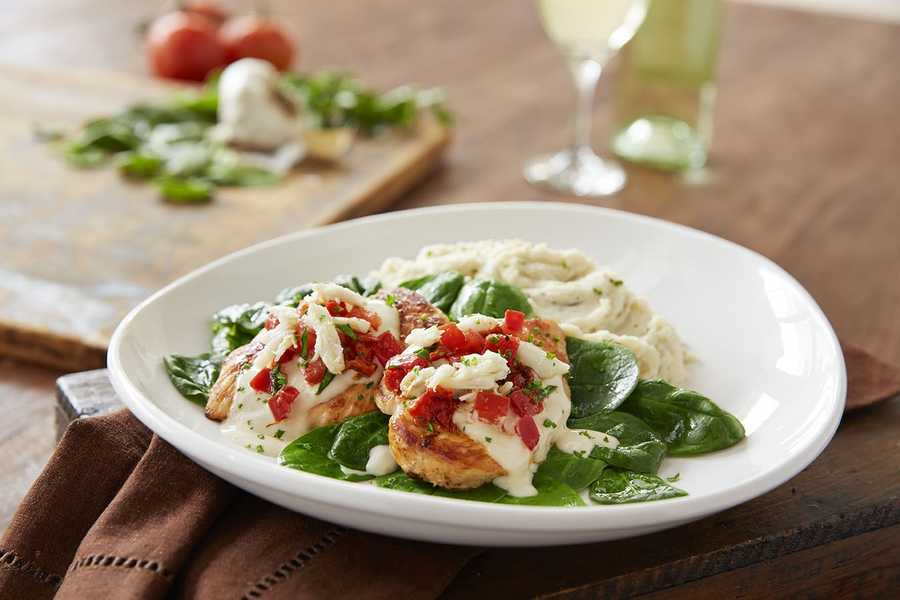 Crab topped chicken features pan-seared chicken breasts topped with crab meat in a lemon cream sauce.  Served with fresh spinach and garlic Parmesan mashed potatoes.