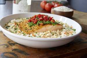 Salmon bruschetta features a grilled salmon filet topped with bruschetta tomatoes and basil pesto, served on freshly prepared seafood risotto with crab meat.