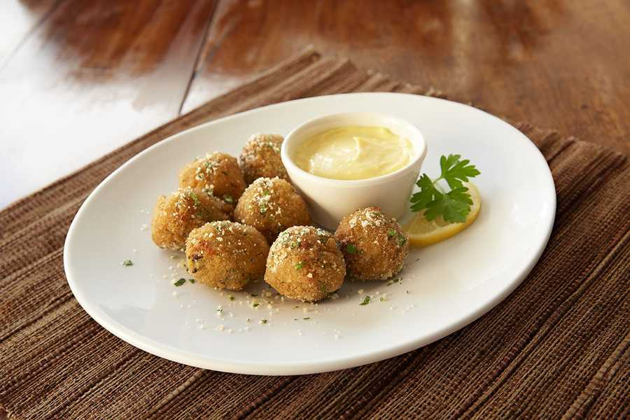 Parmesan olive fritta features a bite-sized blend of olives and Italian cheeses, rolled together and lightly fried. Served with citrus aioli or Gorgonzola cream dipping sauce.