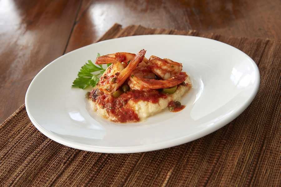 Polenta shrimp alla Grecca features sautéed shrimp served on creamy polenta and topped with a fresh blend of olives, capers and tomato sauce.