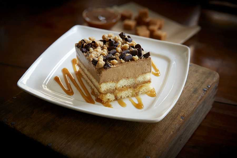 The salted caramel tiramisu features layers of creamy caramel mousse and vanilla-soaked ladyfingers, topped with salted caramel crumble and chocolate shavings.