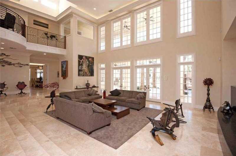 As you enter, you are welcomed by dramatic two-story living spaces accented by floor-to-ceiling windows and balustrade balconies over chiseled travertine floors.