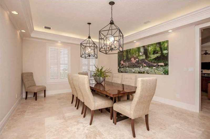 Modern, steel chandeliers are complimented by an artistic wall piece and neutral tones in the dining room.