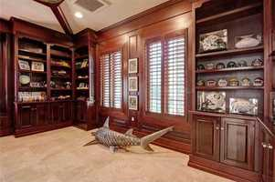 The distinguished library features artfully designed cherry cabinets and plantation shutters which adorn the masculine room.