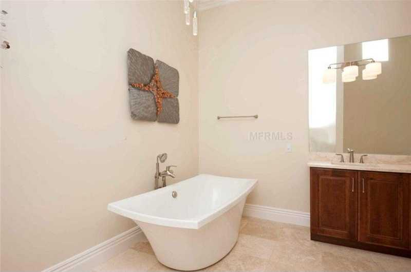 En suite master bathroom features an uncommonly shaped, free-standing tub.