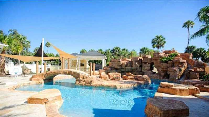 The palatial resort-style grotto pool is enhanced by tropical landscaping, island bridge, waterslide and waterfalls cascading into the pool.