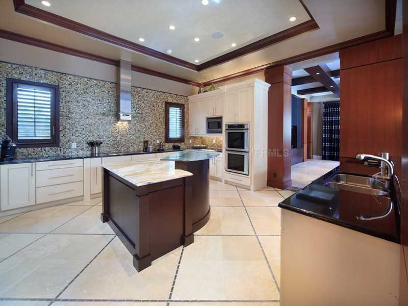Immensely spacious kitchen features an intricate tile back-splash, cooking island, and the top-of-the-line appliances.