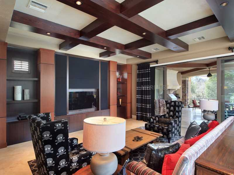 Comfortable family room features a custom entertainment unit.