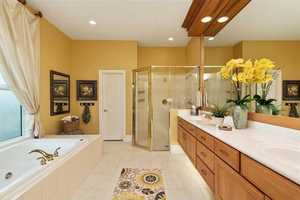The spacious master bathroom features a lengthy spa tub, dual vanity sinks and impressive shower.