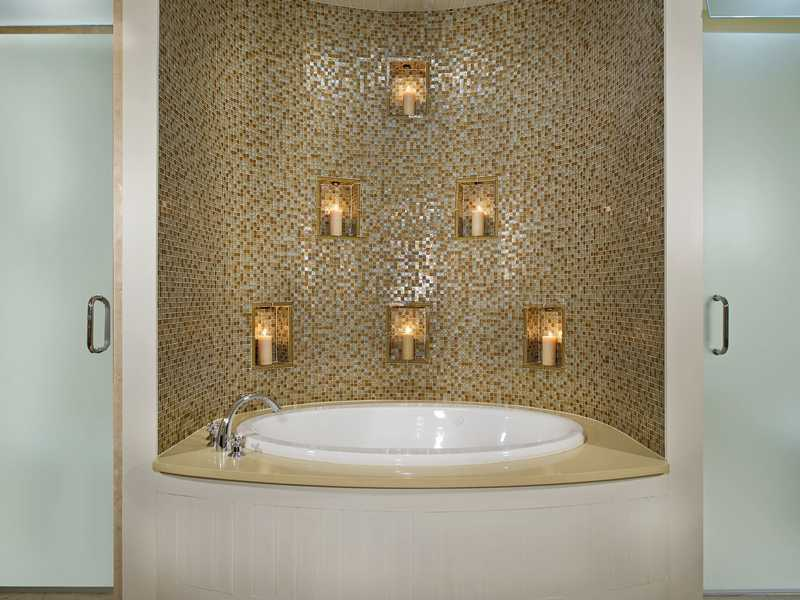 A tiled backsplash and candles inherently create a calming and/or romantic vibe to the master bathroom.