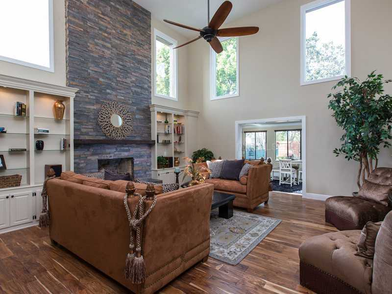 Stone fireplace, built-in bookcases, and the same wood flooring can be seen in the formal living room.