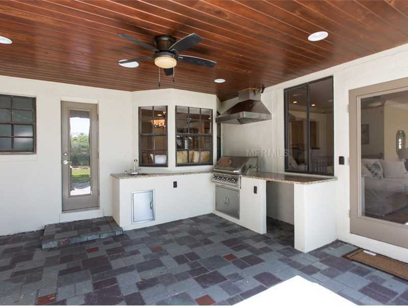 Wood ceiling compliments the covered patio with Summer kitchen.