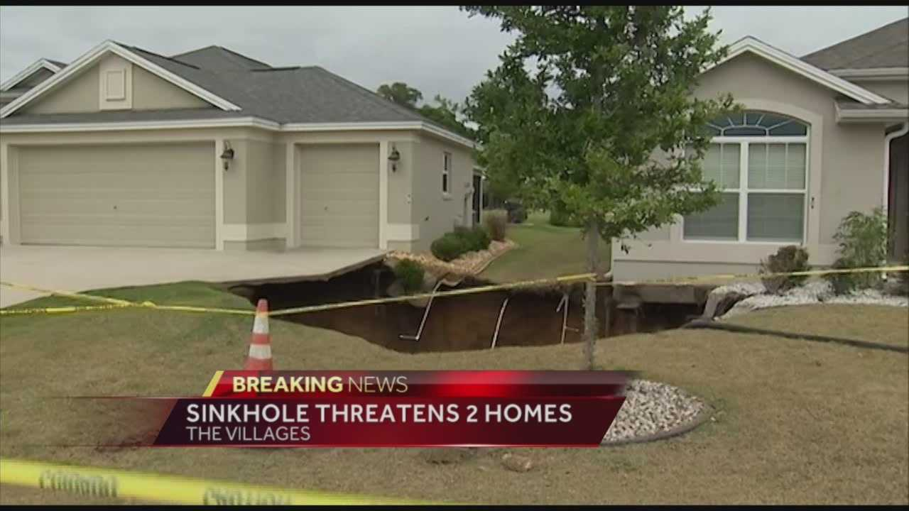 Two homes in the Sumter County section of The Villages are threatened by a sinkhole that grew in size as crews were trying to fill it Saturday.