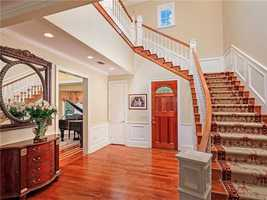 The home's foyer highlights the hardwood maple staircase.