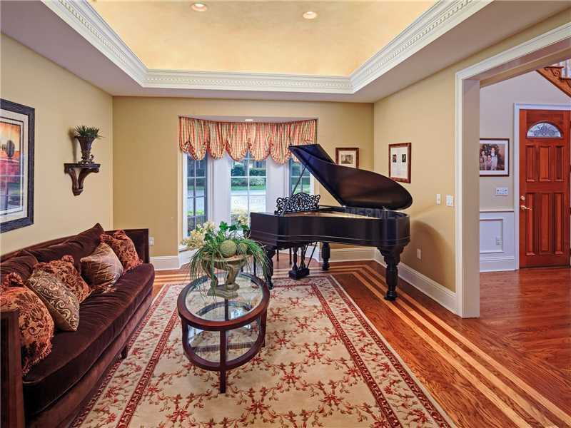 A piano sits near the bay window in the formal living room.