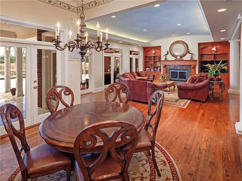 The kitchen, casual dining area and family room are part of an open layout, where four sets of French doors open to the covered porch.