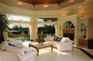See panoramic views of the Lake Nona Golf & Country Club and the property's pool from the formal living room.