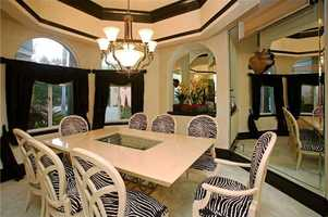 Formal dining room features a floor to ceiling mirror.