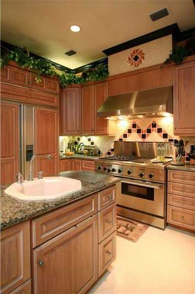 The renovated kitchen features an over-sized granite-topped cooking island, state-of-the-art appliances and custom cabinetry.