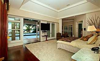 The master suite has an adjacent den with a built-in desk and bookcase. The suite also has pool and lake views.