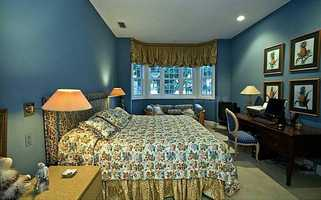 This guest suite also features a bay window, a seating area and a desk.