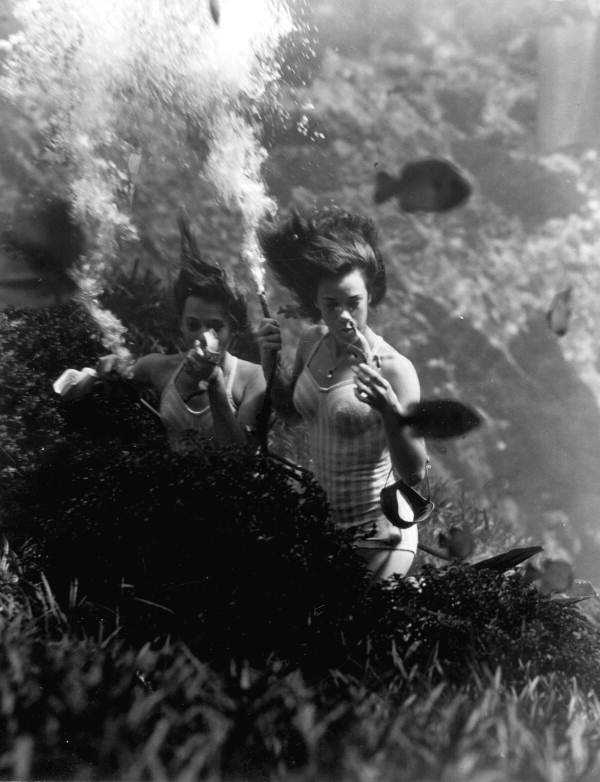 Mermaids demonstrate eating a banana underwater in 1948.