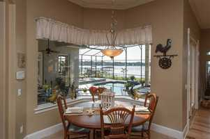 Dining nook has been been built along a bay window looking out over the pool and lake.