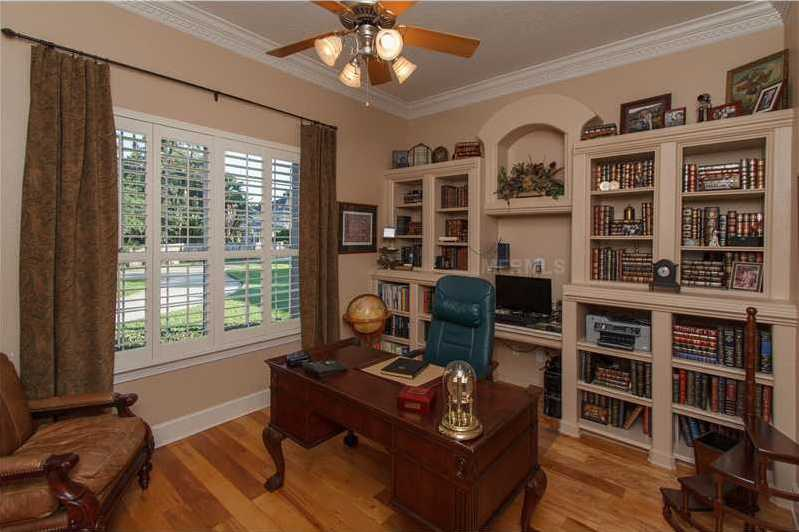 Home office includes a custom wooden bookshelf and desk.