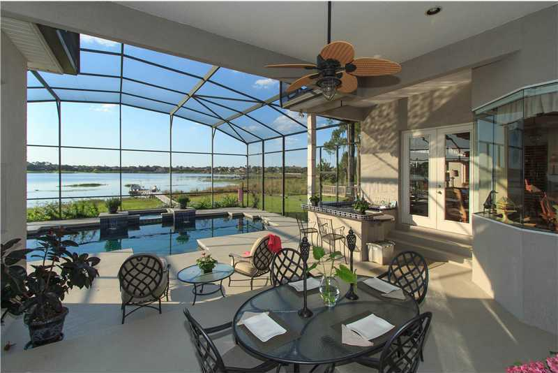 French doors throughout the house lead to the over sized screened pool, heated spa and lanai area equipped with an outdoor kitchen.