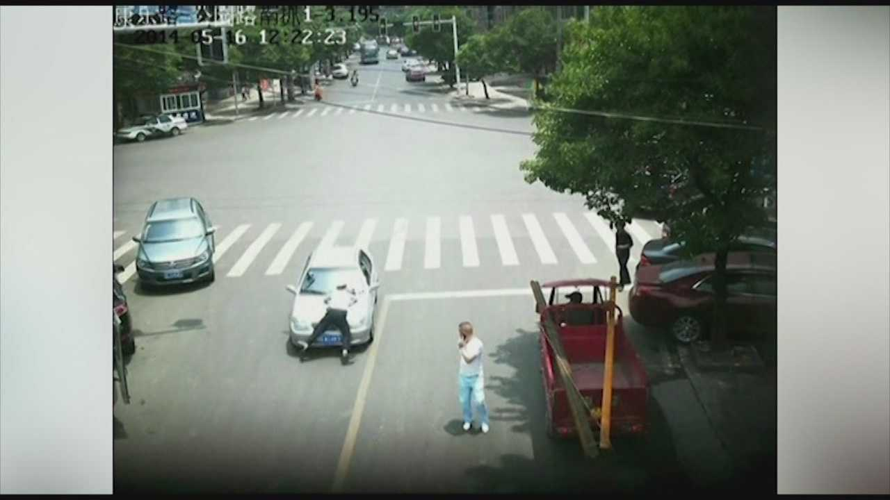 A driver in China tried to flee a traffic stop with the officer clinging to the hood of his car. The officer held on for more than a half mile and was not injured.