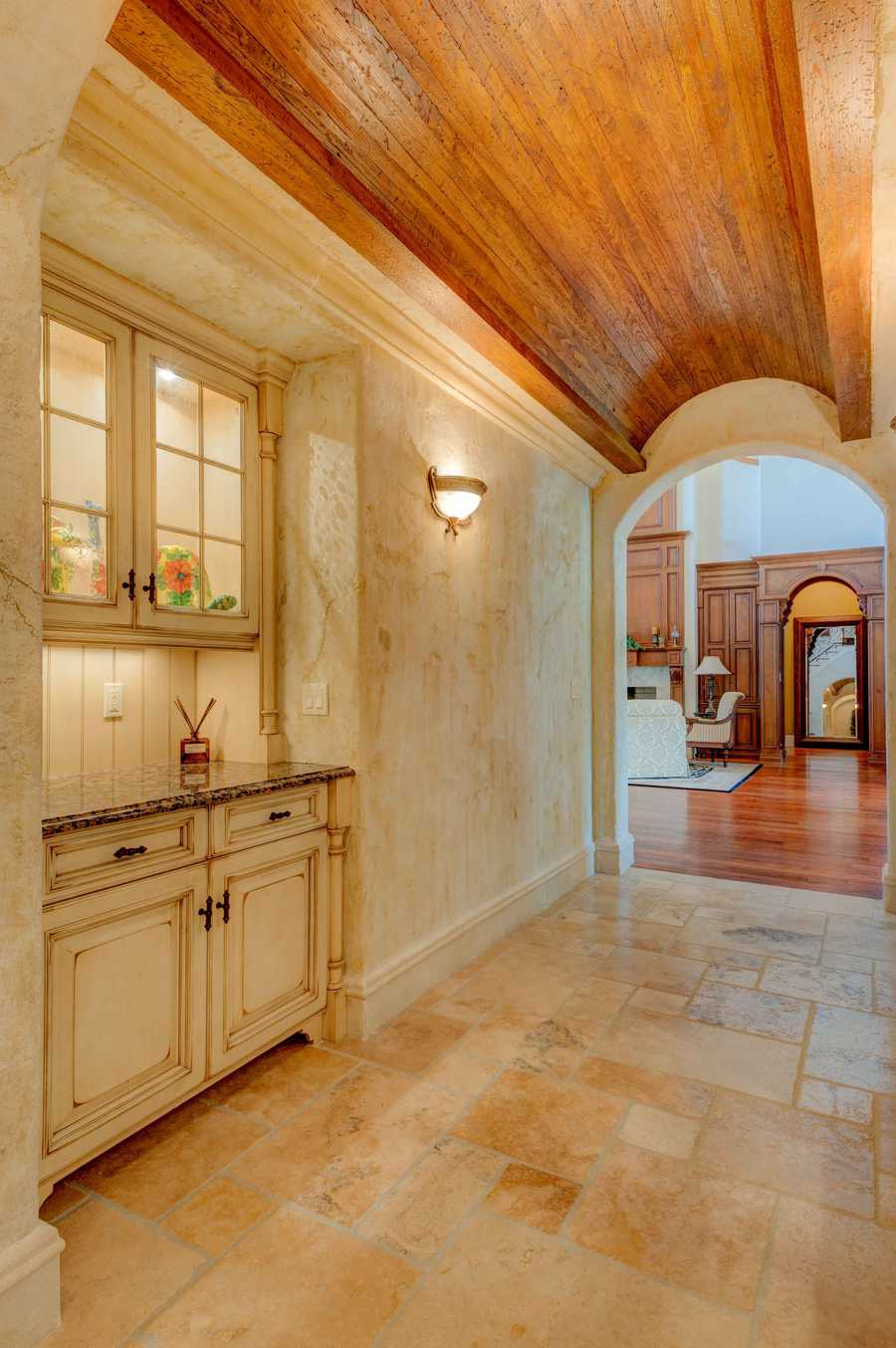 "This unique ""tunnel"" serves as the Butler's Pantry leading to the kitchen, showcasing the Mediterranean architectural style."