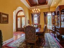 Formal dining room features a grand chandelier and traditional decor.