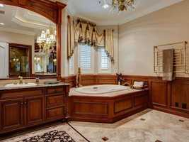 Custom solid wood vanities sit under a glamorous, framed mirror in the master bathroom. The spa tub is also quite large and sits along a bay window.