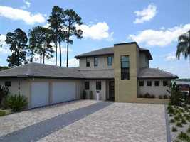 The rear of the home features a sprawling driveway and three-car garage.