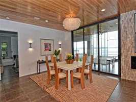 The kitchen nook has a natural wood ceiling and contemporary light fixtures.