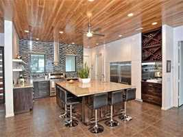 The kitchen has more glamorous undertones than the previous room. It features a massive marble center island with ample bar seating, state-of the art appliances, and a built in wine rack and butler's pantry.