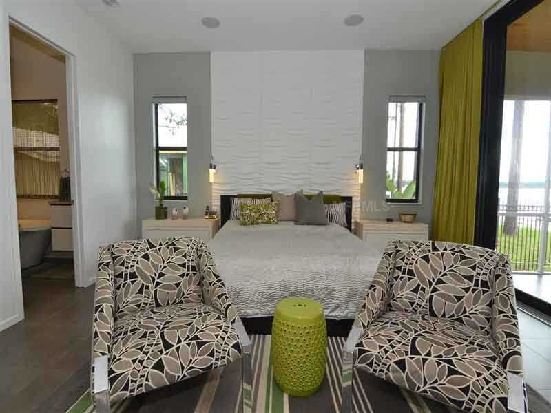 Master bedroom features a brick-like back splash and private balcony.