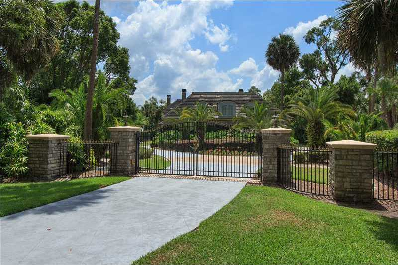 Drive through the private wrought iron gates to a cobblestone motor court & 4 car garage with a full guest apartment above.