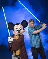"Mark Hamill (""Luke Skywalker"" in the 'Star Wars' film saga) posing with Jedi Mickey Mouse at Disney's Hollywood Studios theme park in Lake Buena Vista, Fla., in June 2014."