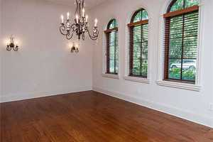 The formal dining room boasts a beautiful chandelier and windows.