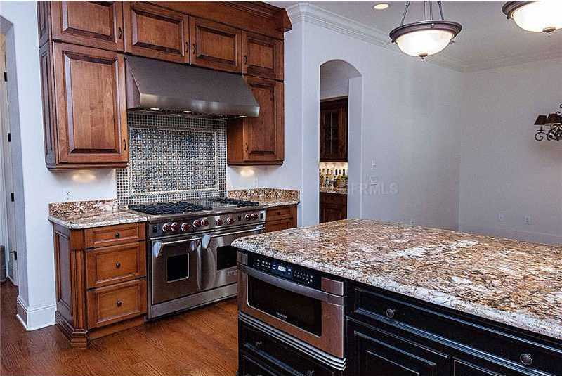 The gas stove is a beautifully adorned by a jewel toned- tile backsplash.
