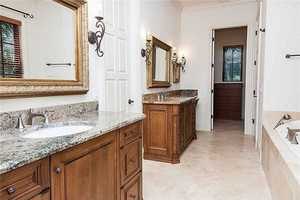 The master bathroom boasts two individual vanities and a massive spa tub.