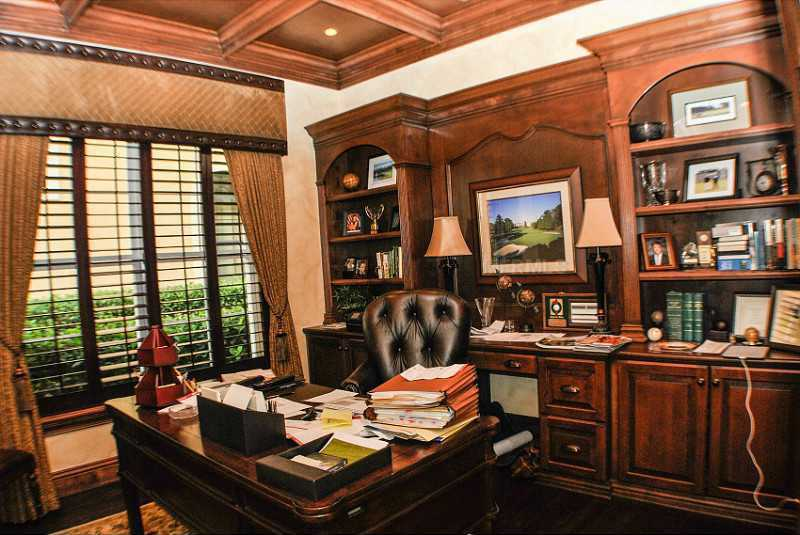Structured wooden ceiling compliments the wooden, custom shelving unit in the home office.