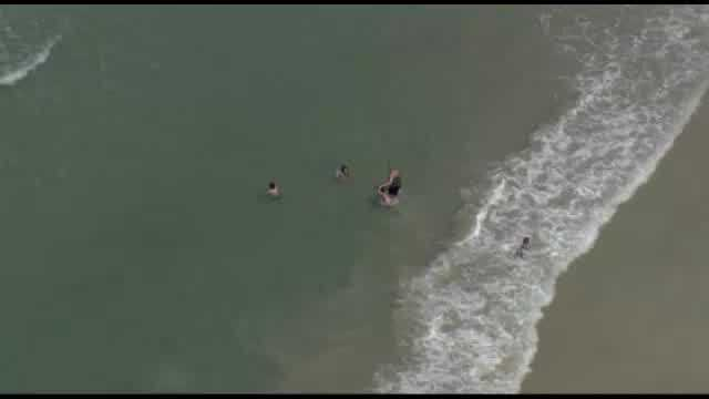 Chopper 2 caught this raw video of a large shark swimming just feet from beachgoers on New Smyrna Beach.