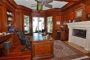 Rich mahogany paneled office/library with fireplace.
