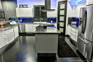 Sophisticated and modern kitchen featuring stainless steel top-of-the-line appliances and a large cooking island.