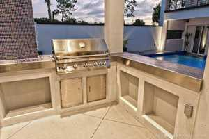 Beautiful outdoor kitchen overlooking the pool and lake views.