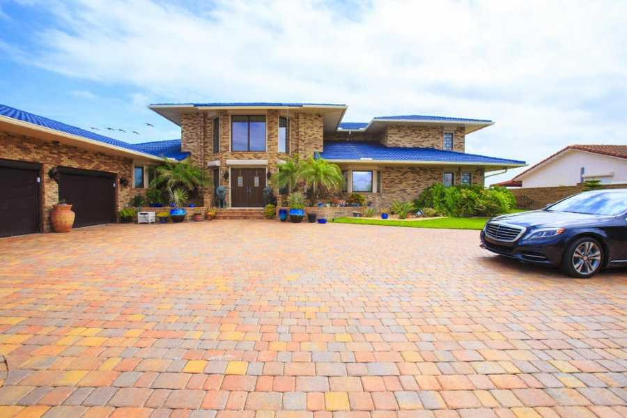 Enter the 125-foot-wide brick walled property through the electronic controlled gate onto the large parking area.