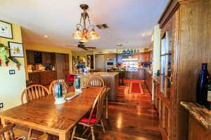 The large kitchen features hardwood cabinets and floors, plus an eat-in casual dining space.