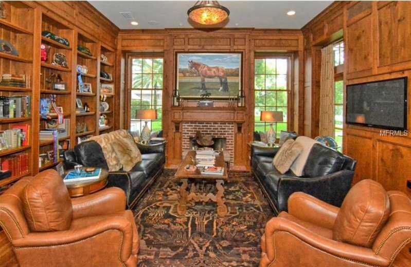 Custom bookshelves and wood paneled walls give this formal living room a refined luxury.